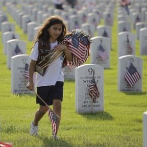 Girl Scout Aurora Ortiz helps place U.S. flags near head stones at Fort Sam Houston National Cemetery in preparation of Memorial Day in San Antonio. (AP)