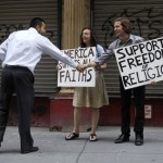 A pedestrian stops to shake Matt Sky's hand while Julia Lundy looks on as they hold signs in front of the site of a proposed mosque near ground zero in New York (AP)