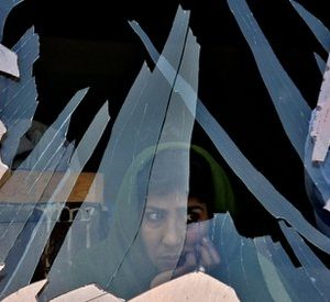 A woman looks out through a destroyed window in Kabul, Afghanistan in front of a cinema near the presidential palace. (AP Photo/Rodrigo Abd)