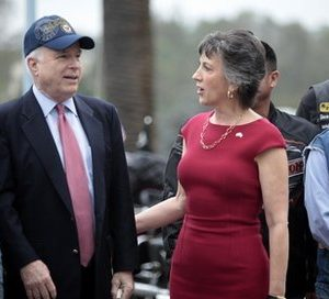 Sen. John McCain, R-Ariz., wears a Navy hat given to him by a member of the Patriot Guard Rider as he and Republican senate candidate Carly Fiorina prepare for group picture in San Diego, Calif. on Saturday, Oct. 16, 2010. (AP Photo/David Brooks, Pool)