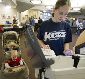 Ginger Bailey of Salt Lake City votes as her twin one-year-old sons, Austin Bailey, front, and Tristan Bailey, back, wait at a library Tuesday, Nov. 2, 2010, in Salt Lake City.  (AP Photo/Jim Urquhart)