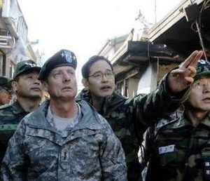 General Walter L. Sharp (L), Commander of United Nations Command, Combined Forces Command, and United States Forces Korea, listens to South Korean military officials as he looks around houses destroyed by North Korean artillery shelling, at a village on Yeonpyeong Island (Reuters Photo)