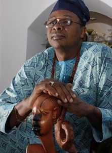 In this Dec. 2, 2010 photo, attorney Bukie O. Adetula rests his hands on a hand-carved West Africa statue as he sits in his home, in Denville, N.J., while wearing traditional clothes of his native Nigeria. (AP Photo/Mel Evans)