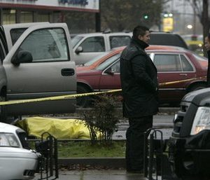 A yellow tarp covers the body of a woman who was killed after being caught in the cross fire between two groups in a strip mall in Sacramento, Calif., Tuesday, Dec. 14, 2010.  Five other people were hurt in the shooting that started when two men walked into a barber shop in the mall and opened fire on two customers.  The customers returned fire and the gunfire strayedinto the parking lot where the victim was loading a child into a care seat.(AP Photo)