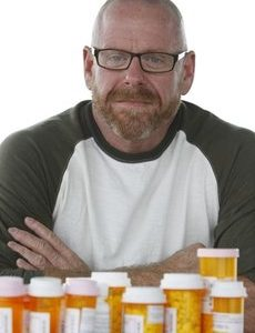 Stephen Farrar poses with some of the medications he must take on a daily basis, in Fort Lauderdale, Fla. Across the country, thousands of HIV-positive people who once would have qualified for state-administered programs that provide free AIDS drugs to low-income people, have been placed on waiting lists or removed from the rolls, as the dismal economy has driven up the need for the program just as states are grappling with budget crises and as people are living longer with HIV. (AP Photo/Wilfredo Lee)
