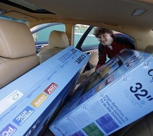 Bert Carpenter, of Jackson, secures two last minute Christmas purchases into his automobile, outside Cowboy Maloney's Electric City appliance store in Jackson, Miss., Friday, Dec. 24, 2010. Carpenter, who admits he is a last minute shopper each Christmas season, purchased the two televisions for his wife and daughter and earlier in the day bought a bike for his son as well as a number of DVDs.  (AP Photo/Rogelio V. Solis)