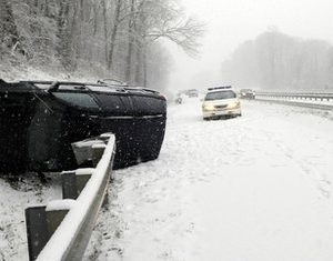 An overturned SUV lies in a snowy ditch along I-40 East in North Carolina at mile marker 48 on Saturday, Dec. 25, 2010. Much of North Carolina was under a winter storm warning. (AP Photo/The Asheville Citizen-Times, Margaret Hester)