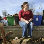Paige Sisemore sits on a foundation of a home after a tornado struck Cincinnati, Ark. (AP Photo)