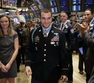 In this Monday, Nov. 22, 2010 file picture, Staff Sgt. Salvatore Giunta, the first living Medal of Honor recipient from the wars in Afghanistan and Iraq, is applauded by traders on the floor of the New York Stock Exchange in New York. (AP Photo/Seth Wenig, File)