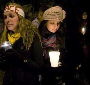 Vera Rapcsak, left, 20, and Lilly Wool, 19, both from Tucson, hold candles outside the office of Rep. Gabrielle Giffords, D-Ariz., Saturday, Jan. 8, 2011, in Tucson, Ariz., as Giffords was shot in the head Saturday by a gunman who opened fire outside a grocery store during a meeting with voters, killing a federal judge and five others in a rampage. (AP Photo/The Arizona Republic, Michael Chow)