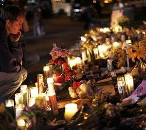 A man looks over the memorial outside the hospital where victims of yesterday's shootings are recovering in Tucson