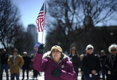 In this March 27, 2010, file photo Virginia Paiva, of Providence, protests against the health care reform bill recently signed into law by President Barack Obama during a rally in front of the Statehouse in Providence, R.I.  Ahead of a vote on repeal in the GOP-led House the week of Jan. 16, 2011, strong opposition to the law stands at 30 percent, close to the lowest level registered in AP-GfK surveys dating to September 2009. The nation is divided over the law, but the strength and intensity of the opposition appear diminished.  (AP Photo/Gretchen Ertl, File)