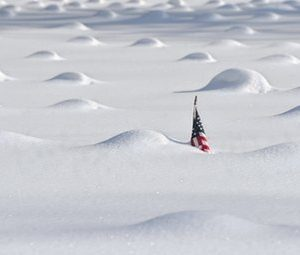n this Jan. 27, 2011 file photo, a flag pokes above the snow around mounds of covered grave markers in Veterans Memorial Field in East Hartford, Conn., after another winter storm. In the Northeast, people are once again reaching for shovels, cities are preparing fleets of snow plows and parents are fretting over a new round of school cancellations as another strong winter storm sweeps in. By now, some winter-weary residents are at last perfecting their pre-storm preparations, not putting much stock in whether Punxsutawney Phil sees his shadow Wednesday morning, Feb. 2 at Gobblers Knob. (AP Photo/Jessica Hill, File)