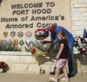 United States Army Specialist Ryan Hill (R) and his daughter Emma, 3, lay flowers and a balloon outside the front gate of the Fort Hood Army Post in Fort Hood, Texas November 7, 2009.   REUTERS/Jessica Rinaldi