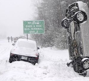 This Feb. 1, 2011 photo shows a car that landed vertically into a snowbank after a multiple vehicle accident on Interstate 93 during a snow storm north of Salem, N.H. No one was injured. (AP Photo/The Eagle-Tribune, Tim Jean)