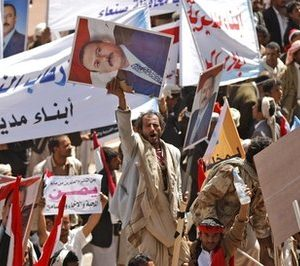 In this Feb. 2, 2011, file photo a supporters of Yemeni President Ali Abdullah Saleh rally, holding his portrait, in Sanaa, Yemen, after the president said he would not seek another term in office or hand power to his son. This in an apparent reaction to protests in this impoverished nation inspired by Tunisia's revolt and the turmoil in Egypt. The unrest engulfing Arab streets and threatening authoritarian governments in the Mideast is complicating U.S. counter terrorism efforts, further shaking the volatile battleground against al-Qaida in Yemen. (AP Photo/Hani Mohammed, File)