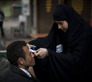 An  Egyptian anti-Mubarak protester receives care from a volunteer nurse next to Tahrir square in Cairo, Egypt, Sunday, Feb. 6, 2011. Egypt's largest opposition group, the Muslim Brotherhood, said it would begin talks Sunday with the government to try to end the country's political crisis but made clear it would insist on the immediate ouster of longtime authoritarian President Hosni Mubarak. (AP Photo / Emilio Morenatti)