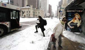 In this Feb. 2, 2011, Gina Alickolli, right, returns to the bus stop shelter to wait for a different bus as another commuter climbs over the snow bank to catch a bus on Michigan Ave. during a blizzard in Chicago. According to an Associated Press-Weather Underground.com poll conducted Jan 21-26 people in the Midwest are most likely to get depressed in the winter. Eighty-three percent of Midwesterners found it a downer. A quarter of those surveyed have canceled a date due to the weather. (AP Photo/Charles Rex Arbogast, File)