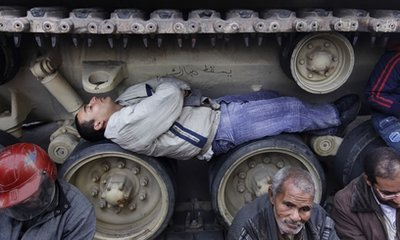 Anti-government protesters sit and lie inside the tracks of an Egyptian Army tank, both to prevent them from moving and to shield themselves from the rain, at the protest site opposite the Egyptian Museum near Tahrir Square in downtown Cairo, Egypt Sunday, Feb. 6, 2011. Egypt's vice president met a broad representation of major opposition groups for the first time Sunday and agreed to allow freedom of the press and to release those detained since anti-government protests began, though Al-Jazeera's English-language news network said one of its correspondents had been detained the same day by the Egyptian military. (AP Photo/Ben Curtis)