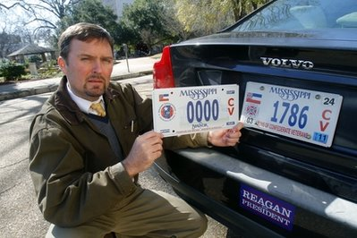 Greg Stewart, a member of the Mississippi Division, Sons of Confederate Veterans, displays a sample of the latest Civil War sesquicentennial tag that is being sold, left, adjacent to the current tag in Jackson, Miss., Tuesday, Feb. 8, 2011. A fight is brewing in Mississippi over a proposal to issue specialty license plates honoring Confederate Gen. Nathan Bedford Forrest, who was an early leader of the Ku Klux Klan. (AP Photo/Rogelio V. Solis)