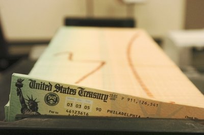 In this Feb. 11, 2005 file photo, trays of printed social security checks wait to be mailed from the U.S. Treasury's Financial Management services facility in Philadelphia. Social Security checks will go out and the troops will remain at post. Furloughed federal workers may get paid late but virtually every essential government agency, like the FBI, the border patrol and the Coast Guard would keep running if the budget standoff leads to a government shutdown. The little-known fact about a government shutdown is this: the government doesn't truly shut down. (AP Photo/Bradley C Bower, File)