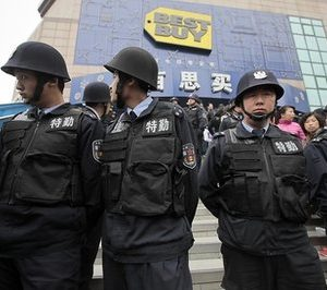 Security guard personnel stand guard as many people line up outside one of the Shanghai outlets Best Buy closed earlier this week to complain or seek help with customer service Friday, Feb. 25, 2011 in Shanghai, China. Minneapolis-based Best Buy opened its flagship store and other outlets in Shanghai just a few years ago, to great fanfare. This week it closed all nine of its brand name stores in China, stunning employees and customers. (AP Photo/Eugene Hoshiko)
