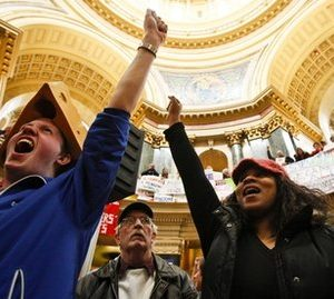 Sean Conard, left, of Green Bay, Wis., and Shyla Deacon of Milwaukee cheer during protests at the state Capitol in Madison, Wis., Saturday, Feb. 26, 2011. Protests to the governor's bill to eliminate collective bargaining rights for many state workers are in their 12th day. (AP Photo/Andy Manis)