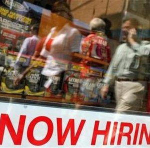 "Pedestrians walk past a ""Now Hiring"" sign in the window of a GNC shop in Boston, Massachusetts September 1, 2010. REUTERS/Brian Snyder"