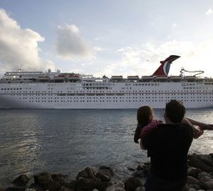 In this Jan. 14, 2011 photo, the Carnival Imagination cruise ship passes South Pointe Park  in Miami Beach, Fla.  as it leaves the Port of Miami. Carnival Corp.'s first-quarter earnings will fall short of Wall Street expectations and the cruise operator is cutting its full-year earnings outlook. (AP Photo/Lynne Sladky)