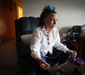 Connie Downey, a former real estate agent who saw her savings erode when she was diagnosed with lung disease sits in her Bellevue, Neb. home. Downey says she is now on the cusp of qualifying for food stamps. (AP Photo/Dave Weaver)