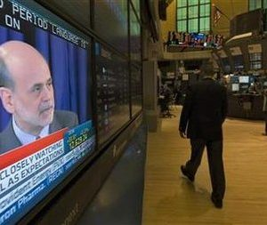 A trader walks past a television screen, displaying Federal Reserve Chairman Ben Bernanke talking at a news conference, at the New York Stock Exchange April 27, 2011.   REUTERS/Mark Dye