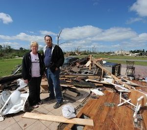 "David Newton, right, and his wife Sharon pose for photos Thursday, April 28, 2011 amid the ruins of their home in Concord, Ala. As Wednesday's tornado was on top of them, David Newton clutched the bathroom's heater vent, his wife clutching his arm. Both held on for their lives. ""If I didn't hold on, I would have gone away with the storm,"" he said. (AP Photo/Wynter Byrd)"