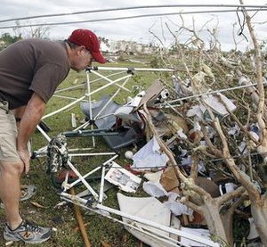 Jerry Stewart looks at some photographs to see if they belong to his son Jonathan Stewart after a tornado hit the day before in Pleasant Grove just west of downtown Birmingham, Ala., Thursday, April 28, 2011. (AP Photo/Butch Dill)