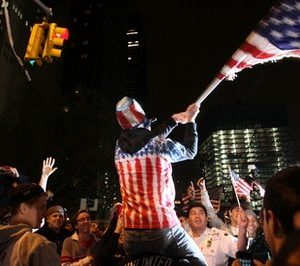 Perched on another's shoulders, Ryan Burtchell, of the Brooklyn borough of New York, center, waves an American flag over the crowd as they respond to the news of Osama Bin Laden's death early Monday morning May 2, 2011 by ground zero in New York.   President Barack Obama announced Sunday night that Osama bin Laden was killed in an operation led by the United States. (AP Photo/Tina Fineberg)