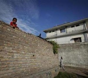 A boy looks over a wall in front of the compound where al Qaeda leader Osama bin Laden was killed in Abbottabad May 3, 2011. Bin Laden lived for the past five to six years in the compound deep inside Pakistan where the al Qaeda leader was killed by U.S. forces, President Barack Obama's counterterrorism adviser said on Tuesday. Bin Laden, who was living in Afghanistan before a 2001 U.S.-led invasion helped topple its Taliban regime, was holed up in a compound in the military garrison town of Abbottabad in Pakistan before Sunday's operation to kill him.   (REUTERS/Faisal Mahmood)