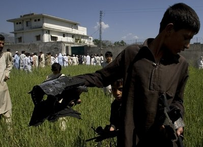 A Pakistani youngster shows metal pieces collected from wheat field outside a house, seen background, where al-Qaida leader Osama bin Laden lived in Abbottabad, Pakistan, on Tuesday, May 3, 2011. Local residents showed off small parts of what appeared to be a U.S. helicopter that Washington said malfunctioned and was disabled by the American commando strike team as they retreated, while Pakistan's leader on Tuesday denied suggestions that his country's security forces had sheltered Osama bin Laden. (AP Photo/Anjum Naveed)