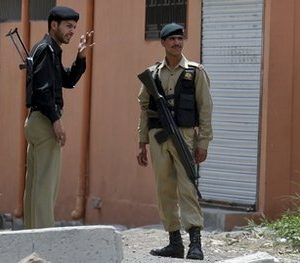 A Pakistan army soldier and a police officer stand guard in a street near the house of former al-Qaida leader Osama bin Laden in Abbottabad, Pakistan on Wednesday, May 11, 2011. Osama bin Laden was killed by a helicopter-borne U.S. military force on last week, in a fortress-like compound on the outskirts of Pakistani city of Abbottabad. (AP Photo/Anjum Naveed)