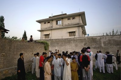Local residents gather outside a house, where al-Qaida leader Osama bin Laden was caught and killed in Abbottabad, Pakistan. The US has stepped up surveillance of operatives previously considered minor players in the al-Qaida infrastructure after reading years of correspondence seized from Osama bin Laden's hideout. The CIA and other counterterror agencies are tracking possible new targets as intelligence experts finish poring over a trove of material that has helped fill in the blanks on how al-Qaida operatives work, think, and where they fit in the organization, three US officials said.     (AP Photo/B.K.Bangash,File)