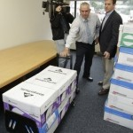 Alaska official Jim Hoff, center, holds a dolly with boxes containing thousands of pages of Sarah Palin's emails as CNN cameraman Jim Castel, left, and CNN correspondent Drew Griffin watch just before the documents were released on Friday, June 10, 2011 in Juneau, Alaska. The emails released Friday were first requested during the 2008 White House race by citizens and news organizations, including The Associated Press. (AP Photo/Brian Wallace)