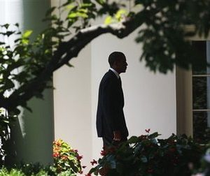 A silhouetted President Barack Obama walks back to the Oval Office of the White House  in Washington, Friday, June, 24, 2011, following his arrival on Marine One helicopter. (AP Photo/Pablo Martinez Monsivais)