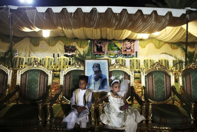 In this photo taken on a government-organized tour, children sit in front of a picture of Libyan leader Moammar Gadhafi before a group wedding party held for 25 couples in support of Moammar Gadhafi at his Bab al-Aziziya compound in Tripoli, Libya, Thursday, July 7, 2011. NATO denied a Libyan government charge Thursday that the alliance is intentionally using its airstrikes to assist rebel advances, saying it is sticking to its mandate to protect civilians. (AP Photo/Tara Todras-Whitehill)