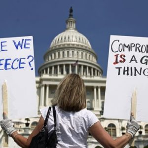 A demonstrator holds placards to protest U.S. debt in front of the Capitol in Washington. REUTERS/Kevin Lamarque