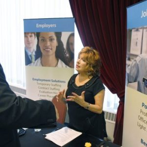 Donna Ciora, an employment specialist with Express Employment Professionals, right, talks with people attending the Pittsburgh Career Fair, in Pittsburgh. Fewer people sought unemployment benefits last week, though the drop was small and not enough to signal much improvement in the job market. (AP Photo/Keith Srakocic)
