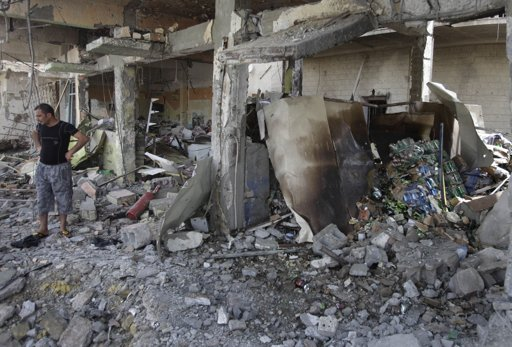 An Iraqi man inspects a destroyed liquor store after a bomb attack in Baghdad, Iraq, Thursday, July 28, 2011. (AP Photo/Karim Kadim)