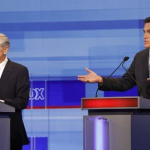 Republican presidential candidates former Massachusetts Gov. Mitt Romney speaks as Rep. Ron Paul, R-Texas, listens during the Iowa GOP/Fox News Debate at the CY Stephens Auditorium in Ames, Iowa, Thursday, Aug. 11, 2011. (AP Photo/Charlie Neibergall, Pool)