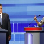 Republican presidential candidate Michele Bachmann (R) gestures beside Mitt Romney during the Republican presidential debate in Ames, Iowa August 11, 2011. REUTERS/Charlie Neibergall/Pool