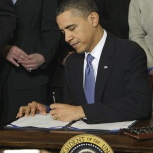 In this March 23, 2010 file photo, President Barack Obama signs the health care bill in the East Room of the White House in Washington. A federal appeals court panel struck down the requirement in President Barack Obama's health care overhaul package that virtually all Americans must carry health care insurance or face penalties. (AP Photo/J. Scott Applewhite, File)