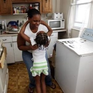 "Tashawna Green, 21, helps her daughter Taishaun, 6, down from the washing machine after posing for a portrait at her home in Queens Village, New York August 21, 2011. Green who up until recently worked 25 hours a week at Target, is on food stamps and says a good number of her colleagues are too. Green made $8.08 cents an hour working for Target. ""It's a good thing that the government helps, but if employers paid enough and gave enough hours, then we wouldn't need to be on food stamps."" (REUTERS/Jessica Rinaldi)"