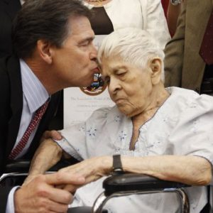 Gov. Rick Perry, left, kisses, Elvira Rocha-Cisneros, right, the mother of Marine Cpl. Roy Cisneros as he presents the Texas Legislature Medal of Honor, Thursday, Sept. 1, 2011, in San Antonio. Cpl. Cisneros died while serving in Vietnam.(AP Photo/Eric Gay)