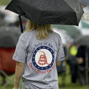 An unidentified Tea Party supporter waits in the rain for former Alaska Gov. Sarah Palin to speak to Tea Party members during the Restoring America event Saturday, Sept. 3, 2011, in Indianola, Iowa. (AP Photo/Charlie Neibergall)